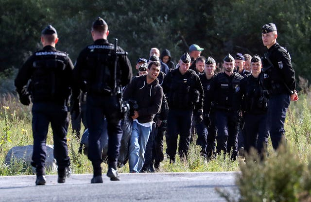 French police officers move migrants on from a camp in Calais