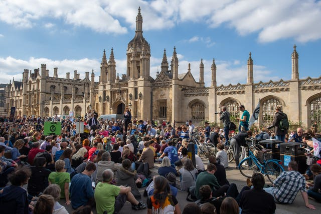 Protesters sit down in the street in front of King's College at the UK Student Climate Network's Global Climate Strike in Cambridge