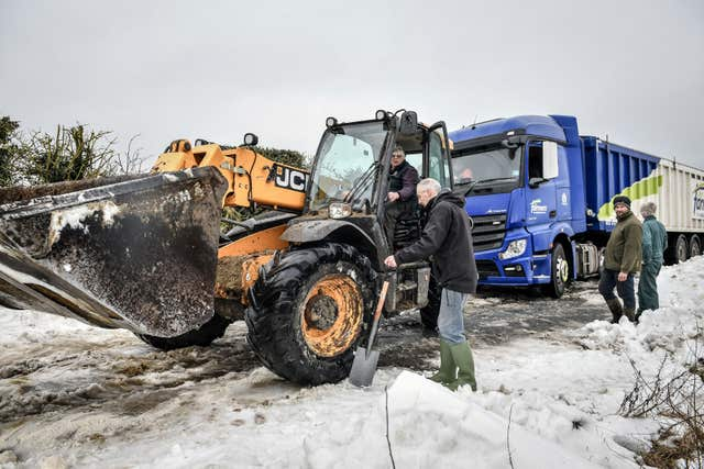 A JCB machine tries to tow a lorry stuck in snow near Marlborough, WIltshire (Ben Birchall/PA)