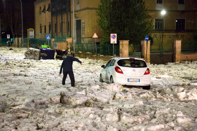 A man tries to reach a car blocked by ice after a hailstorm hit Rome