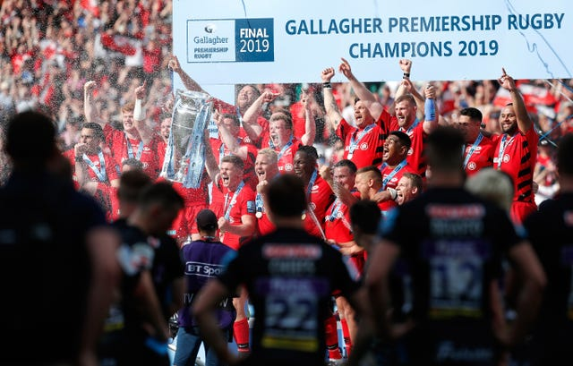 Saracens lift the 2019 Premiership trophy while Exeter players watch on