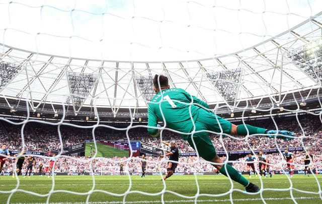 Manchester City's Sergio Aguero scores alongside West Ham United's Lukasz Fabianski