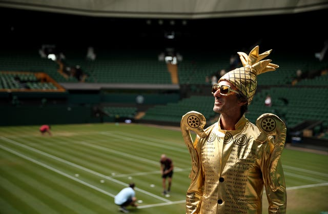 Fan Chris Fava, dressed as the men's singles trophy, made a Centre Court appearance on Monday