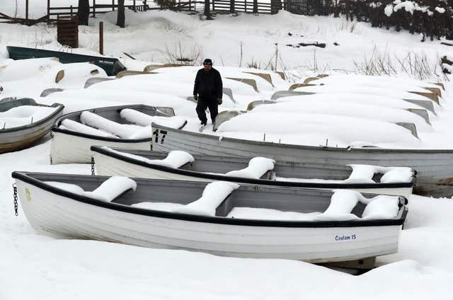 Jimmy Feeney from the Carron Valley Fishery inspects his snow covered boats near Stirling, following the recent severe weather (Andrew Milligan/PA)