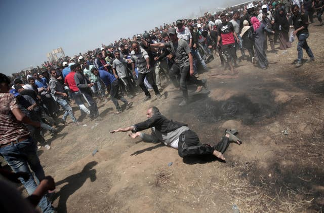 An elderly Palestinian man falls on the ground after being shot by Israeli troops during a deadly protest at the Gaza Strip's border with Israel (Khalil Hamra/AP)