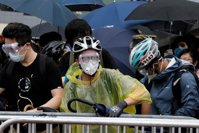 Protesters wear protection gear as they gather near the government headquarters