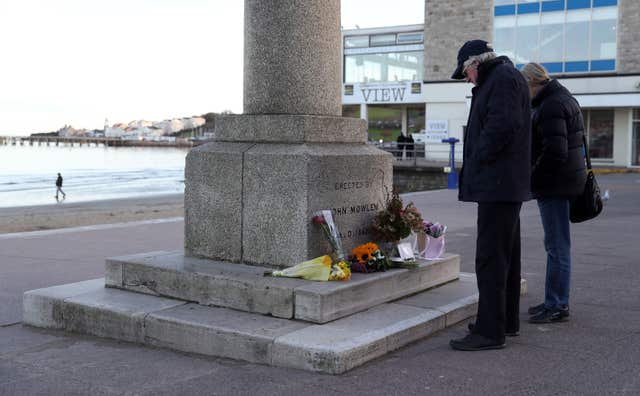 Tributes left at the King Alfred Monument on the seafront in Swanage