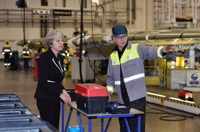 Theresa May speaks to a worker during a visit to the Bombardier factory (Charles McQuillan/PA)
