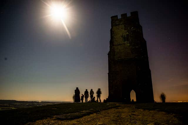 People watch a blood red supermoon in the skies above Glastonbury Tor