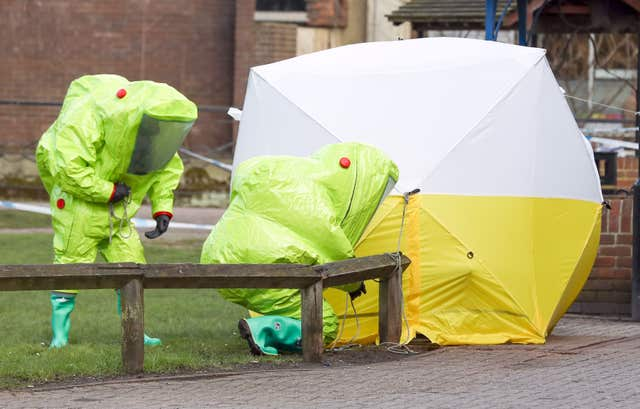 Personnel in hazmat suits work to secure a tent covering a bench in the Maltings shopping centre in Salisbury, where former Russian double agent Sergei Skripal and his daughter Yulia were found critically ill by exposure to a nerve agent (Andrew Matthews/PA)