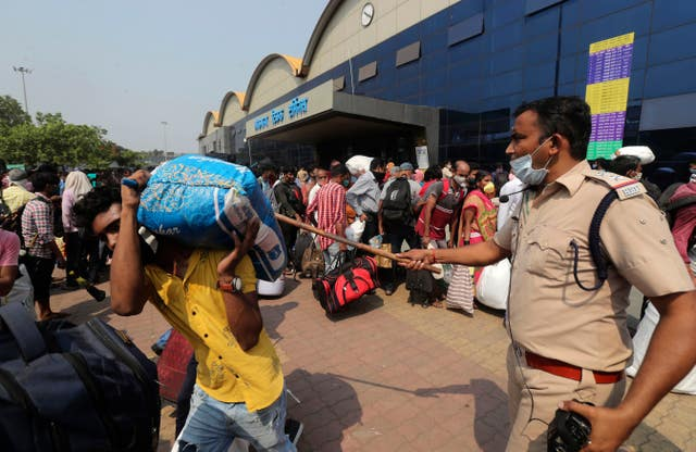 A police officer controls a crowd waiting to board trains at Lokmanya Tilak Terminus in Mumbai, India