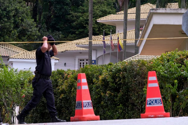 A police officer guards the entrance road to the residence of Najib Razak in Kuala Lumpur (Sadiq Asyraf/PA)
