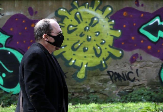 A man wearing a mask walks past coronavirus-related graffiti in Edinburgh