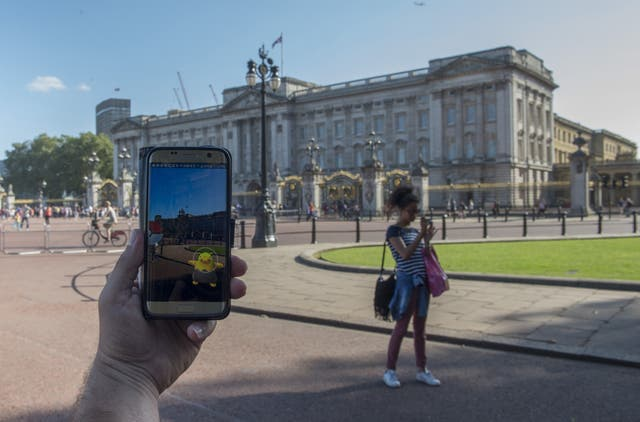 People playing the Pokemon Go reality game on their phone outside Buckingham Palace in London.