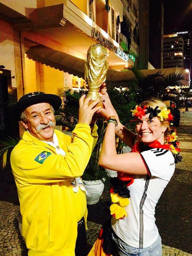 Clovis Acosta Fernandes, also known as Gaucho da Copa, holding a replica World Cup with the German fan he gave the cup to after the 7-1 defeat to Germany in 2014