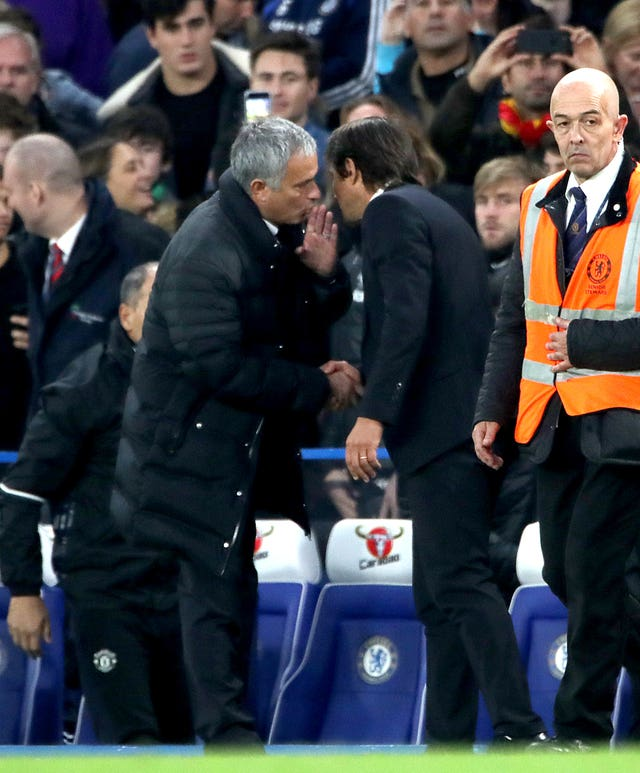 Manchester United manager Jose Mourinho whispers something to Chelsea boss Antonio Conte