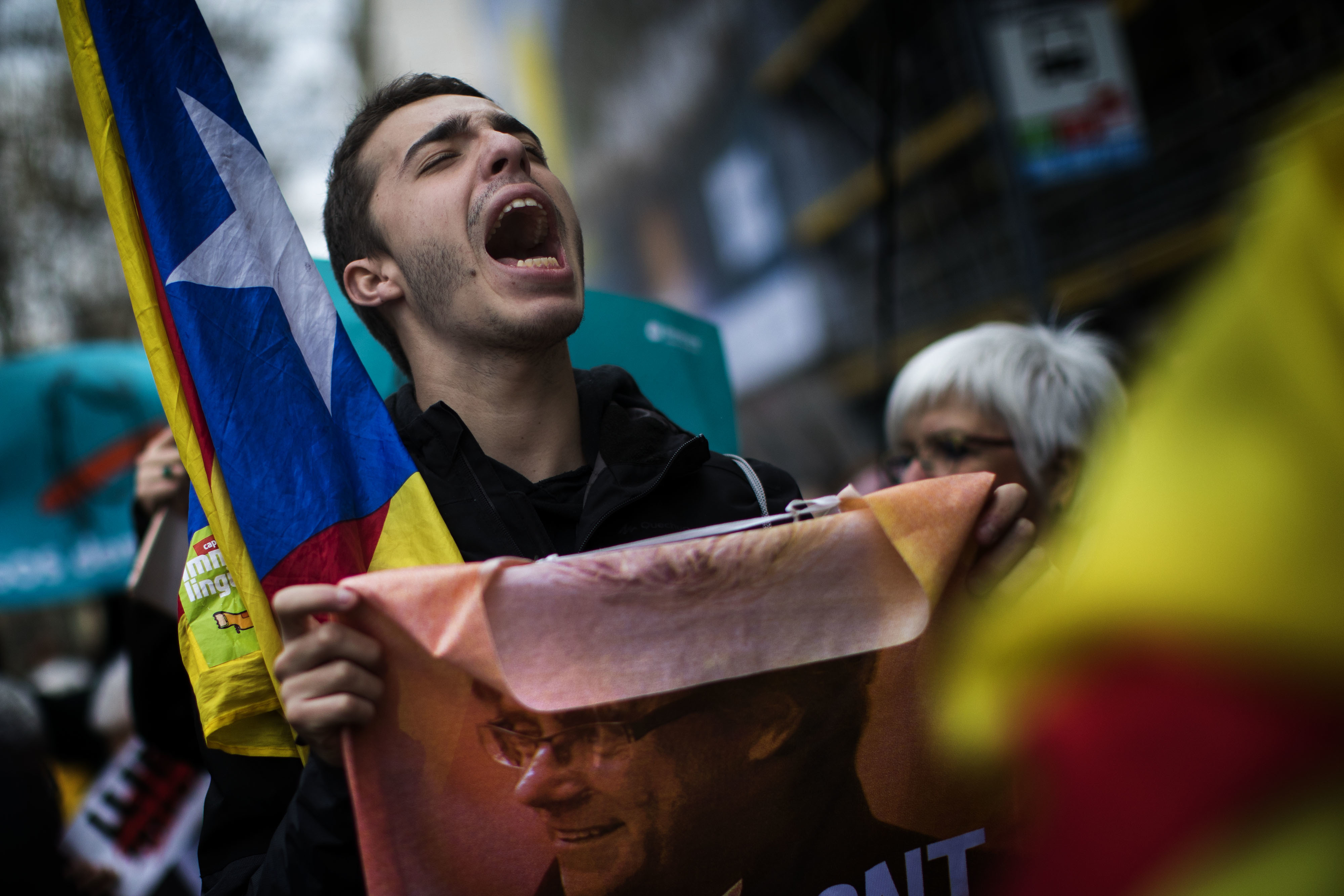 A pro-independence demonstrator holds a poster with