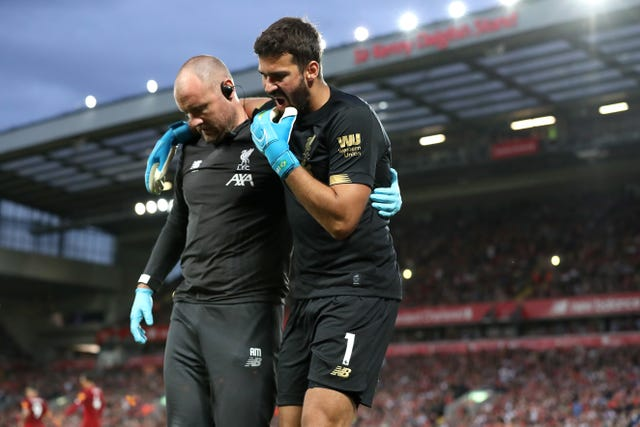 Alisson Becker, right, is helped off the pitch against Norwich