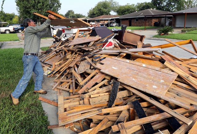 Jesus Ramirez after removing damaged wooden flooring from his home in Houston (David J, Phillip/AP)