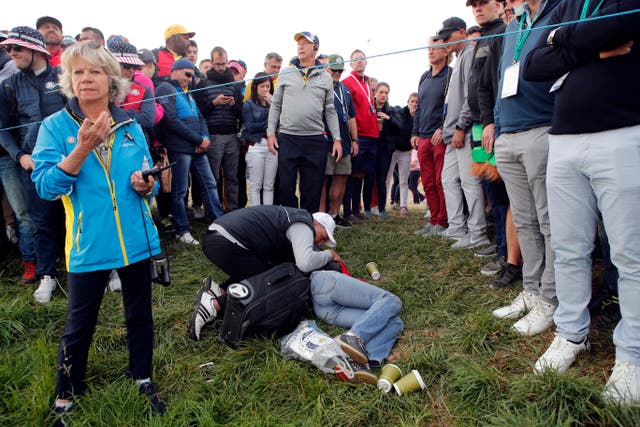 A man tends to the injured woman after she was hit by a wayward tee shot