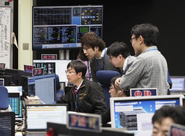 Staff of the Hayabusa2 Project watch monitors for a safety check at the control room of the JAXA Institute of Space and Astronautical Science in Sagamihara, near Tokyo