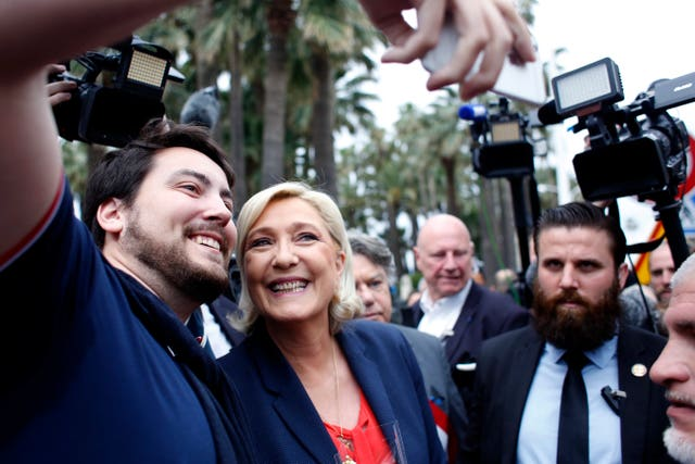 Marine Le Pen poses for a selfie after laying a wreath (Thibault Camus/AP)
