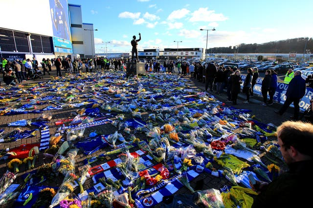 Fans look on at the flowers and scarves placed outside Cardiff City Stadium in tribute to Emiliano Sala