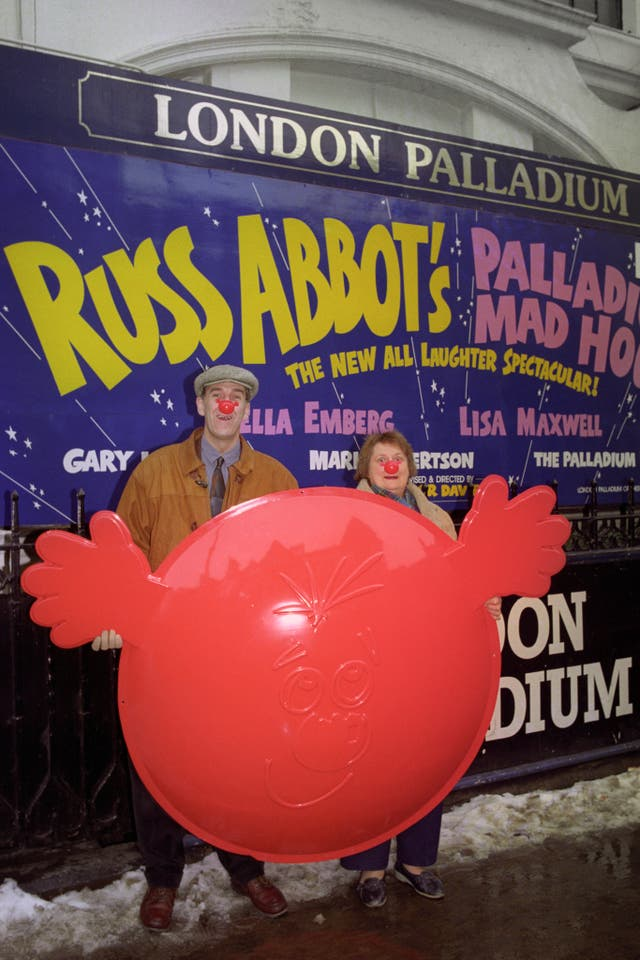 Russ Abbot and Bella Emberg hoist a giant Comic Relief red nose up outside the London Palladium (Michael Stephens/PA)