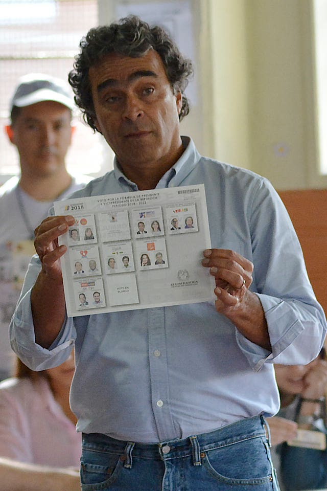 Sergio Fajardo shows his ballot before voting (AP Photo/Luis Benavides)