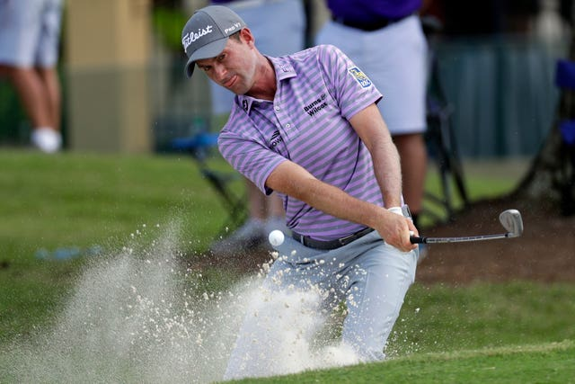 Webb Simpson plays out of a bunker at the 16th hole