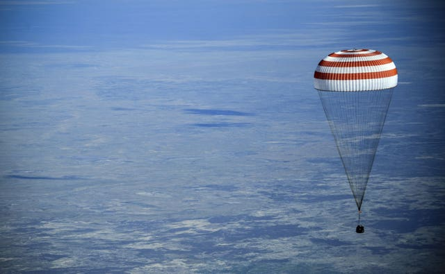 The Soyuz space capsule descends about 90 miles south-east of the Kazakh town of Zhezkazgan