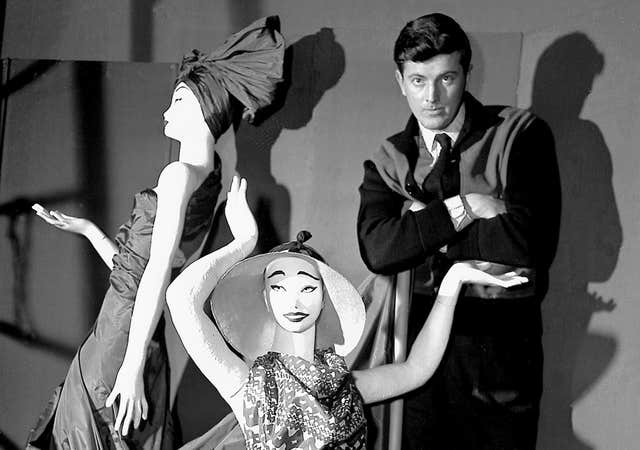 Givenchy poses with mannequins in his shop in Paris in 1952 (AP)