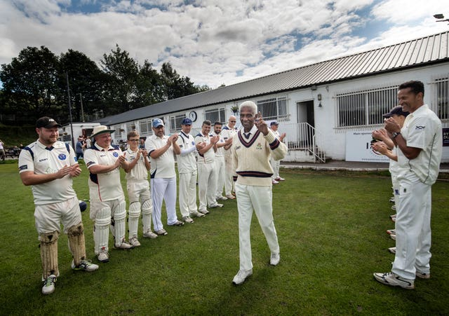 Players form a guard of honour as 85-year-old Cecil Wright walks onto the pitch ahead of playing his last game of competitive cricket at Uppermill Cricket Club in Oldham