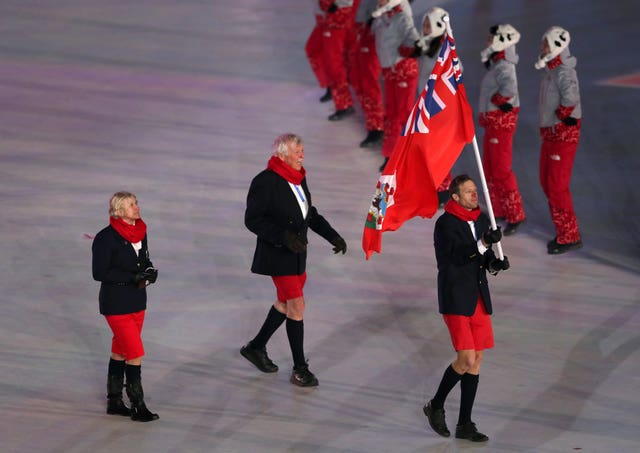 Flag bearer Tucker Murphy leads Bermuda into the Winter Olympics opening ceremony, in his shorts