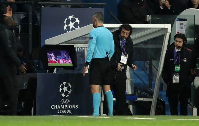 Referee Damir Skomina checks video footage on a monitor before awarding a late penalty to Manchester United
