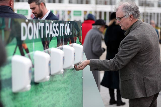 Racegoers use sanitiser to keep their hands clean at Cheltenham Festival