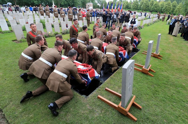 Soldiers carry the coffins of two young privates and an unknown soldier, who fought during the First World War, during a burial service at Hermies Hill British Cemetery, near Albert, France