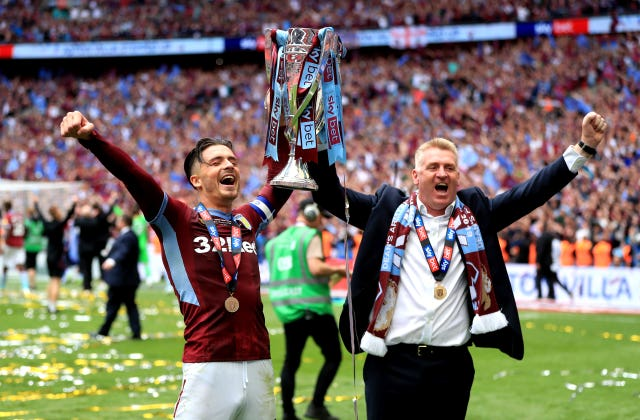 Dean Smith, right, and captain Jack Grealish lift the Championship play-off trophy