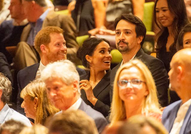 Harry and Meghan take their seats beside Lin Manuel Miranda