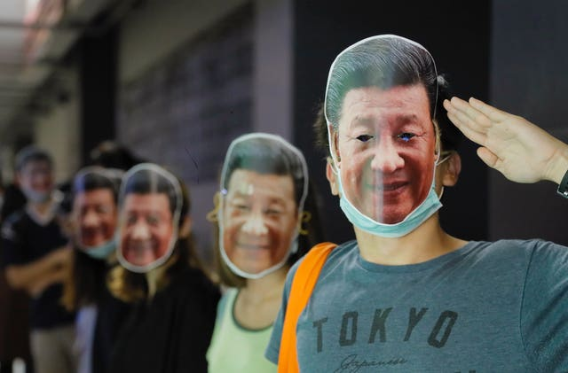 Protesters wear masks of President Xi Jinping