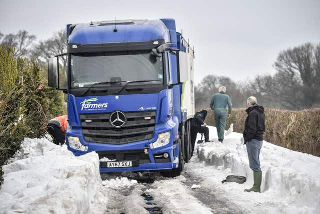 Men use shovels to try and free a lorry near Marlborough, Wiltshire (Ben Birchall/PA)