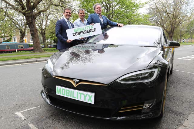 Martin Shanahan, CEO of IDA, left, Philip McNamara, VP of Voxpro and Dan Kiely, CEO of Voxpro, right, with a Tesla Model S car at a launch event for the MobilityX self-driving conference (Niall Carson/PA)