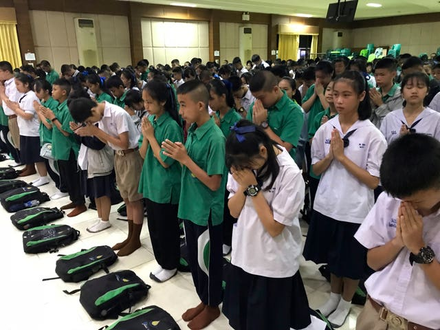 Students pray at Maesaiprasitsart school where six of the rescued boys study