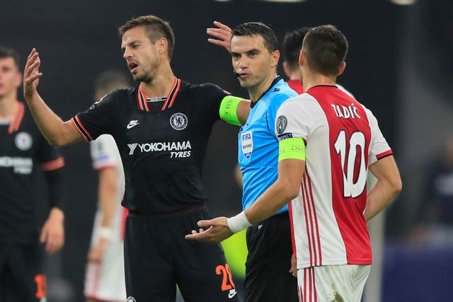 Chelsea's Cesar Azpilicueta, left and Ajax's Dusan Tadic talk to the referee