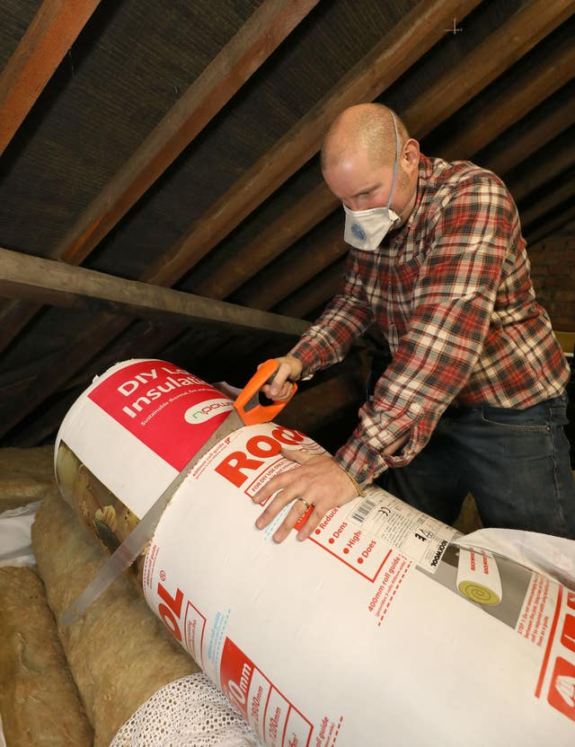 Richard Burr installing loft insulation (Philip Toscano/PA)