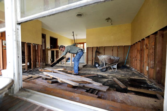 Jesus Ramirez works on his home after it was damaged in Hurricane Harvey