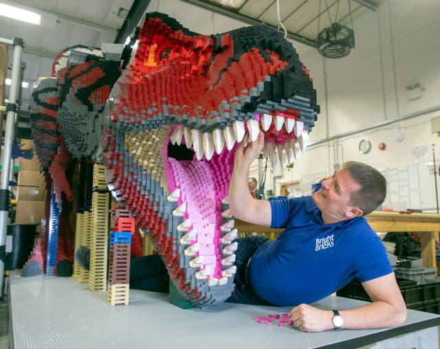 Bright Bricks member of staff Ed Diment works on a life-size T-Rex made out of Lego