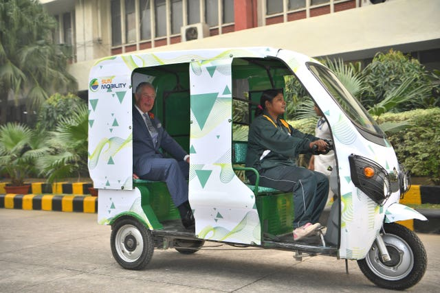 The Prince of Wales is given a demonstration of an e-rickshaw at the Indian MET office in New Delhi