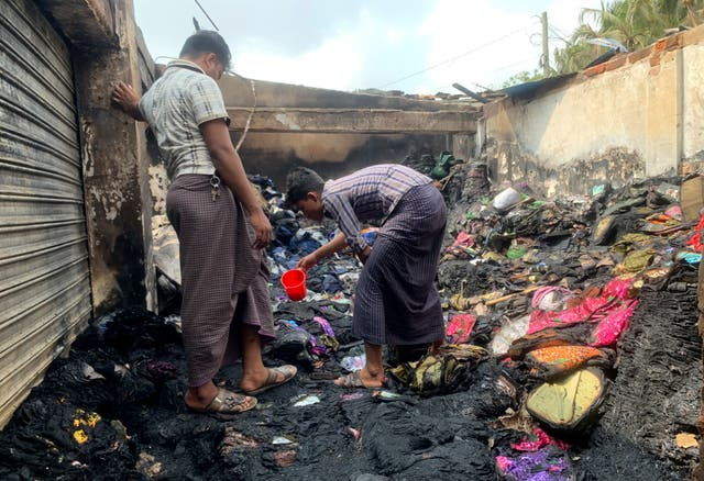 People inspect the debris after the fire in the makeshift market
