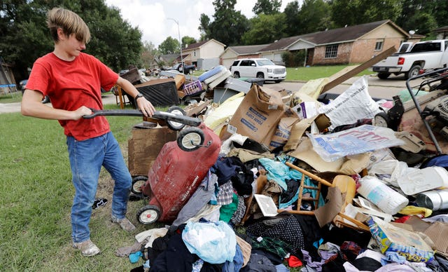 Volunteer Alex Brewer removing items from the home of Julia Lluvia (David J. Phillip/AP)